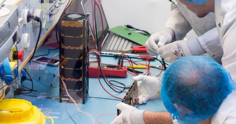 Integration of the nanosatellite TRISAT into a QuadPack